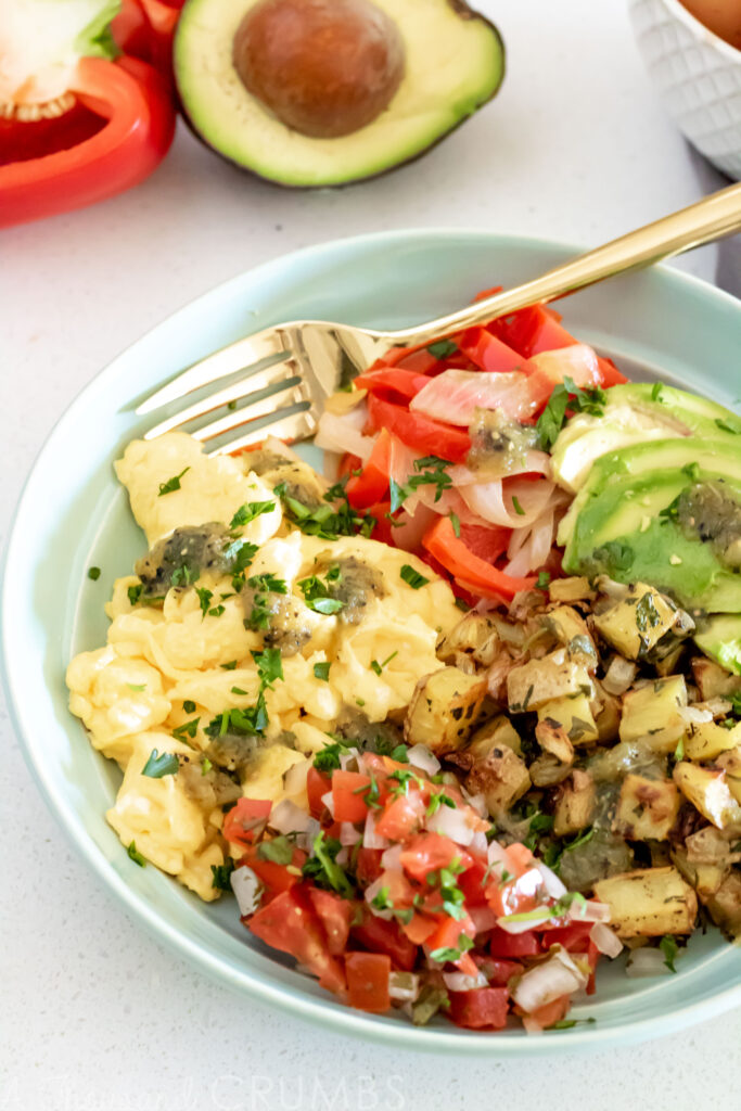 A healthy, gluten free and dairy free, breakfast bowl full of fluffy scrambled eggs, roasted potatoes, avocado, and two different kinds of salsa. #athousandcrumbs #breakfast #healthybreakfast #glutenfreebreakfast #dairyfree #healthyeating