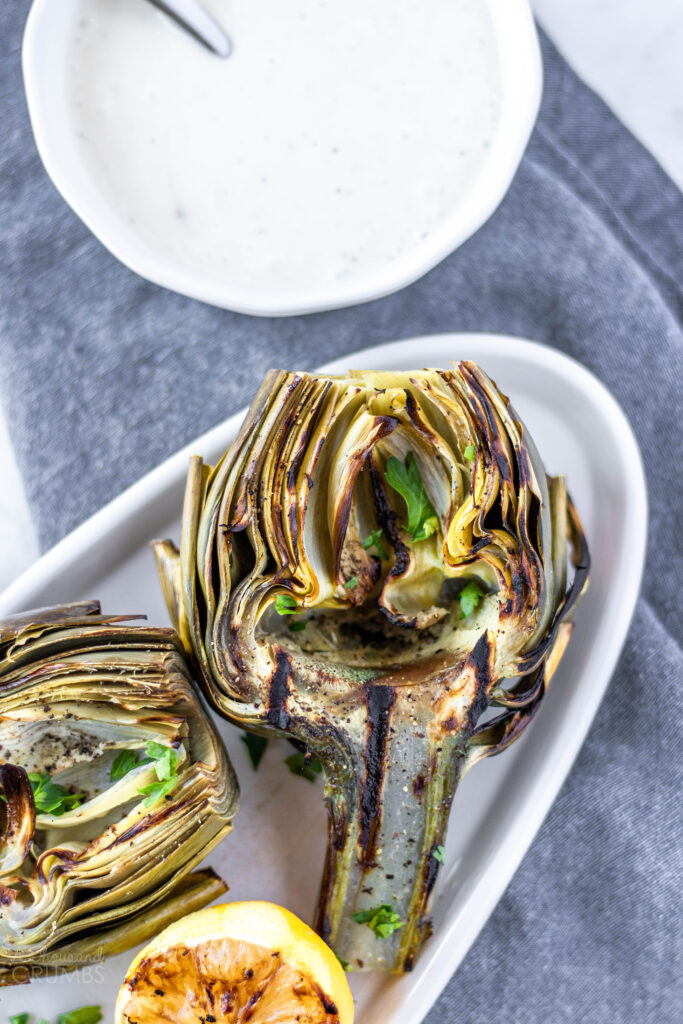 Delicious grilled artichokes with a zesty lemon garlic dipping sauce. A beautiful artichoke appetizer or side dish. #athousandcrumbs #grilled #artichokes #lemongarlic #dippingsauce